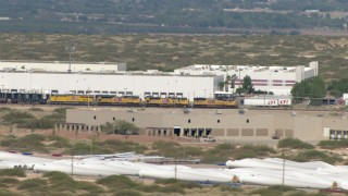 AF0001_000919 - HD stock footage aerial video of a train passing a large warehouse building in El Paso, Texas