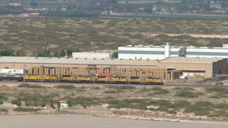 AF0001_000920 - HD stock footage aerial video of a train cruising past warehouse buildings in El Paso, Texas