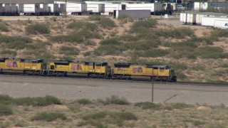AF0001_000921 - HD stock footage aerial video of a train passing by many parked semi-trailers, El Paso, Texas