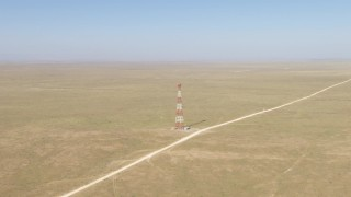 AF0001_000960 - HD stock footage aerial video approach a tower by a dirt road in a desert plain near El Paso, Texas