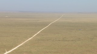 AF0001_000961 - HD stock footage aerial video of a dirt road through a wide desert plain near El Paso, Texas