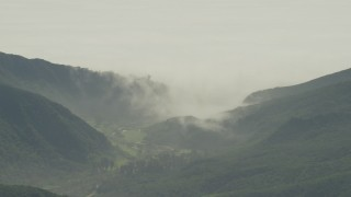 AF0001_000974 - Aerial stock footage of Fog rolling over green mountains and reveal suburban homes in Los Angeles, California