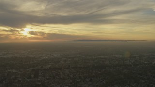 AF0001_000976 - 5K stock footage aerial video of urban neighborhoods and Downtown Los Angeles skyline seen from Santa Fe Springs, California at sunset