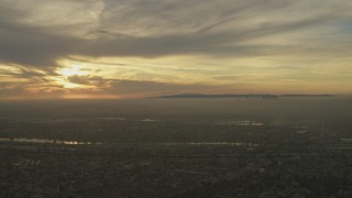 AF0001_000979 - 5K stock footage aerial video of setting sun behind clouds and Downtown Los Angeles skyline seen from Whittier, California