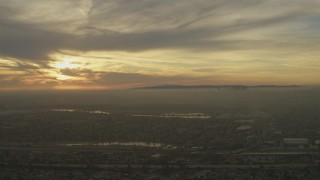 AF0001_000980 - 5K stock footage aerial video of setting sun behind clouds and Downtown Los Angeles skyline seen from Pico Rivera, California