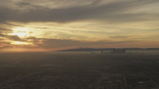 AF0001_000983 - Aerial stock footage of The setting sun behind clouds and the Downtown Los Angeles skyline, California
