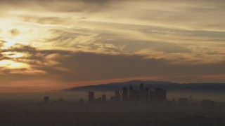 AF0001_000987 - Aerial stock footage of Sunset-lit clouds above the Downtown Los Angeles skyline in haze, California