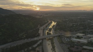 AF0001_001007 - 5K stock footage aerial video of heavy traffic on 134 and I-5 by the Los Angeles River and neighborhoods at sunset, Burbank, California