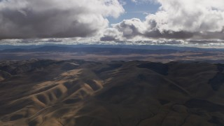 AF0001_001014 - Aerial stock footage of Godrays and clouds over desert hills in Southern California