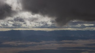 AF0001_001017 - Aerial stock footage of Dark clouds over desert and mountain ridges in Southern California