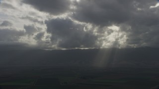 AF0001_001025 - Aerial stock footage of Godrays shining down on farm fields in Southern California