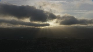 AF0001_001029 - Aerial stock footage of Godrays shining from behind clouds onto homes in Southern California at sunset