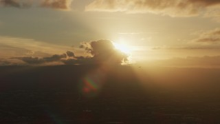 AF0001_001032 - 8K stock footage aerial video of setting sun behind clouds as a helicopter passes in Southern California