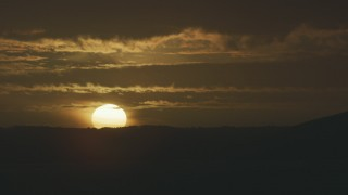 AF0001_001043 - 8K stock footage aerial video of a view of the setting sun behind a mountain ridge, revealing an airport control tower, in Northern California