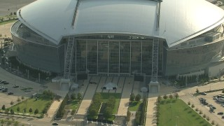 AI05_DAL_07 - 1080 aerial stock footage video zoom out from flags, revealing AT&T Stadium, Arlington, Texas