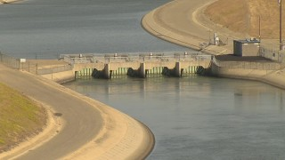 AI06_FRM_008 - 1080 stock footage aerial video flying by a dam spanning an aqueduct, zoom out, Central Valley, California