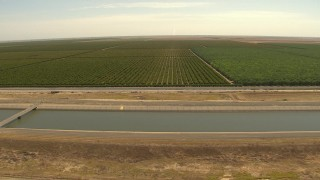 AI06_FRM_009 - 1080 stock footage aerial video an aqueduct near rows of crops, Central Valley, California