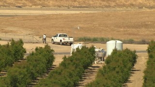 AI06_FRM_027 - 1080 aerial stock footage video a man getting into his truck, near aqueduct and orchard, Central Valley, California