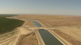 AI06_FRM_059 - 1080 stock footage aerial video approaching an irrigation canal, crops, open fields, Central Valley, California
