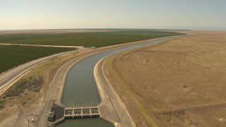 AI06_FRM_060 - 1080 stock footage aerial video following an aqueduct between orchards and open fields, Central Valley, California