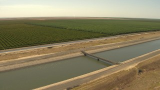 AI06_FRM_062 - 1080 stock footage aerial video orbiting an irrigation canal near farmland, Central Valley, California