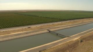 AI06_FRM_062 - 1080 stock footage aerial video orbiting an irrigation canal near farmland, Central Valley, California