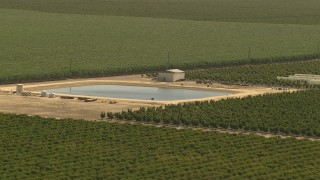 AI06_FRM_065 - 1080 stock footage aerial video flying by manmade pond, surrounded by farmland, Central Valley, California