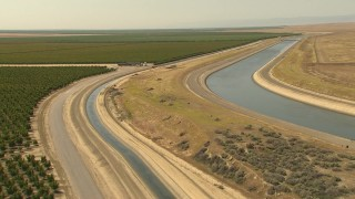 AI06_FRM_066 - 1080 stock footage aerial video flying along aqueduct near farmland, Central Valley, California