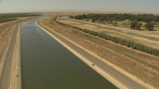 AI06_FRM_086 - 1080 stock footage aerial video flying over aqueducts, bordered by trees, Central Valley, California
