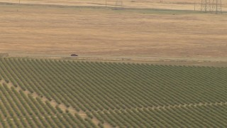 AI06_FRM_124 - 1080 stock footage aerial video track cars on a highway near orchard, Central Valley, California