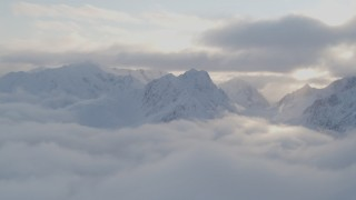 AK0001_0010 - 4K stock footage aerial video pan by snow covered peaks above low clouds, Chugach National Forest, Alaska