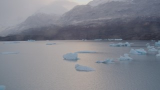AK0001_0044 - 4K stock footage aerial video shoreline, reveal icebergs, snow covered mountains, Inner Lake George, Alaska
