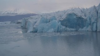 AK0001_0050 - 4K stock footage aerial video flying low over a lake, panning right past a glacier, Knik, Alaska