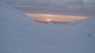 AK0001_0090 - 4K stock footage aerial video approach snow covered summit, reveal sunset, Chugach Mountains, Alaska, sunset