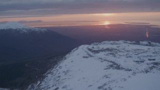 AK0001_0092 - 4K stock footage aerial video snowy slope, reveal Alpenglow at Arctic Valley, Chugach Mountains, Alaska, sunset