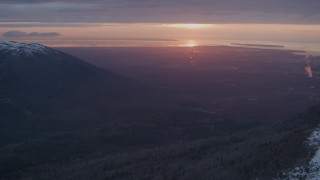 AK0001_0094 - 4K stock footage aerial video snow covered slope, revealing Anchorage, Chugach Mountains, Alaska, sunset