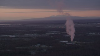 AK0001_0100 - 4K stock footage aerial video flyby power plant, zoom to reveal Downtown Anchorage, Alaska, sunset