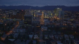 AK0001_0156 - 4K stock footage aerial video revealing Hotel Captain Cook, Downtown Anchorage, Alaska, night