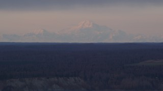 AK0001_0163 - 4K stock footage aerial video flying by forest countryside, snow capped mountains, Point MacKenzie, Alaska