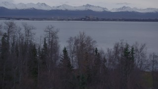 AK0001_0173 - 4K stock footage aerial video over wooded shoreline, reveal Downtown Anchorage, Point MacKenzie, Alaska