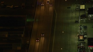 AK0001_0207 - 4K stock footage aerial video following East 5th Avenue, tracking a police car, Anchorage, Alaska, night