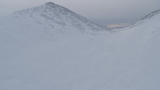 AK0001_0231 - 4K stock footage aerial video ascend snowy peak, reveal snow capped mountains, Chugach Mountains, Alaska