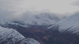 AK0001_0257 - 4K stock footage aerial video fly past snow covered, cloud capped peaks of the Chugach Mountains, Alaska