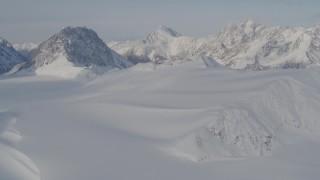 AK0001_0275 - 4K stock footage aerial video fly over snowy valley, pan across the mountain peaks, Chugach Mountains, Alaska