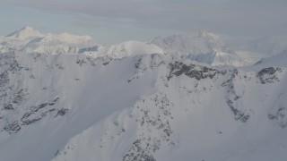 AK0001_0277 - 4K stock footage aerial video approach snowy range, revealing a distant valley, Chugach Mountains, Alaska
