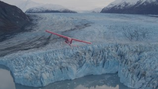 AK0001_0284 - 4K stock footage aerial video tracking seaplane over a glacier, lake, Inner Lake George, Alaska