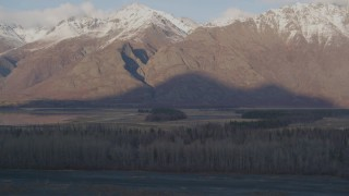 AK0001_0289 - 4K stock footage aerial video tilting down over trees, revealing river and Swan Lake, Alaska