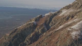 AK0001_0293 - 4K stock footage aerial video ascend rocky slope of lightly snow covered peak, Chugach Mountains, Alaska