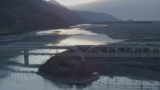 AK0001_0303 - 4K stock footage aerial video lift off shore, follow Knik River, Old Glenn Highway bridge, Knik River, Alaska, sunset