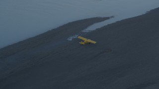 AK0001_0308 - 4K stock footage aerial video tracking small plane landing on river bank, Knik River, Alaska, twilight